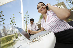 Businesswoman On Call With Colleague In Background Royalty Free Stock Images