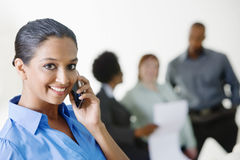 Businesswoman On Call With Colleagues Discussing In The Background Stock Photos