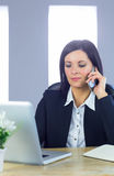 Businesswoman on a call at her desk Stock Image