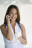 Businesswoman On Call Holding Takeout Coffee Royalty Free Stock Photography