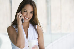 Businesswoman On Call Holding Takeout Coffee Royalty Free Stock Images