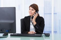 Businesswoman on call while using computer at desk Royalty Free Stock Image