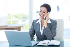 Businesswoman on call and using her laptop Royalty Free Stock Images