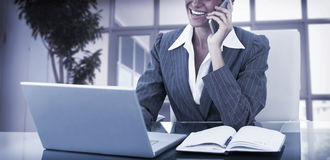 Businesswoman on call and using her laptop Stock Photo