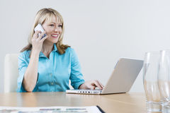 Businesswoman On Call While Using Laptop Stock Photo
