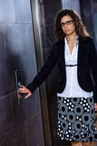 Businesswoman calling elevator Stock Photo