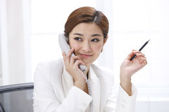 Businesswoman calling by a fixed line phone Stock Photos