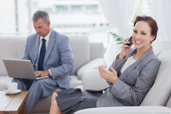 Businesswoman calling while her colleague working on his laptop Stock Photos