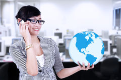 Businesswoman calling and holding a globe Stock Photo