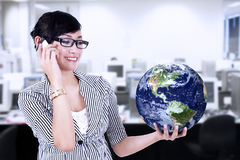 Businesswoman calling and holding world globe Royalty Free Stock Photography