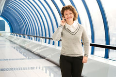 Businesswoman calling phone. Cheerful woman calling cellular phone on the bridge stock images