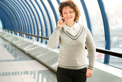 Businesswoman calling phone. Cheerful woman calling cellular phone on the bridge royalty free stock photography