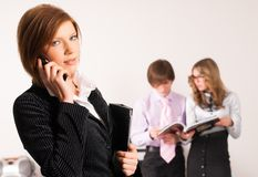 Businesswoman calling by phone in office Stock Photography