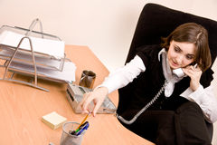 Businesswoman calling by phone at office Stock Photography