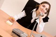 Businesswoman calling by phone at office Stock Image