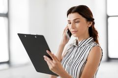 Businesswoman calling on smartphone at office. Business people, technology and corporate concept - businesswoman or realtor with clipboard calling on smartphone Stock Photography