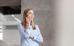 Businesswoman calling on smartphone at office Royalty Free Stock Photo