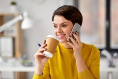 Businesswoman calling on smartphone at office stock photo