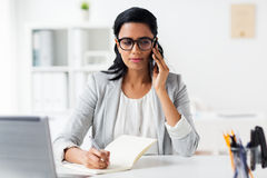 Businesswoman calling on smartphone at office Stock Photos