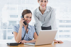 Businesswoman calling and smiling at camera with co worker Stock Images