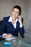 Businesswoman calling and write notes Stock Photography