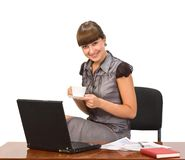 Businesswoman with cap of coffee and laptop. Young attractive smiling businesswoman drinking coffee at coffee-break Royalty Free Stock Photography