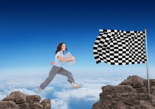 Businesswoman with carpet jumping on the rocks to arrive to the checker flag. Digital composite of businesswoman with carpet jumping on the rocks to arrive to Stock Photo