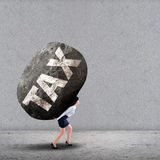 Businesswoman carrying a big rock of TAX Stock Photo