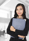 Businesswoman carrying a book. Young businesswoman smiling and carrying a book in the office Royalty Free Stock Image