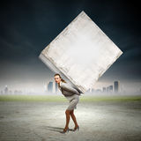 Businesswoman carrying cube Royalty Free Stock Image