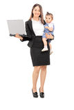 Businesswoman carrying her daughter and holding a laptop Royalty Free Stock Image