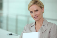 Businesswoman carrying laptop Stock Images