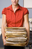 Businesswoman carrying stack of file folders Stock Image