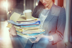 Businesswoman carrying stack of file folders. While using mobile phone in office Royalty Free Stock Photography