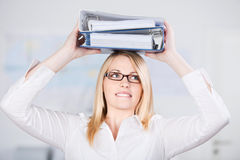 Businesswoman Carrying Two Binders On Head Royalty Free Stock Image