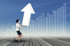 Businesswoman carrying upward arrow Stock Photography