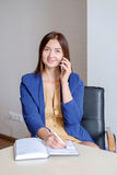 Businesswoman in casual wear taking mobile phone call and writing notes into calendar at office desk. Royalty Free Stock Photo