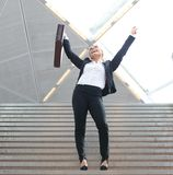 Businesswoman celebrating arms outstretched on staircase Stock Photos