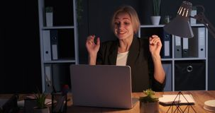 Businesswoman celebrating online success at night office. Businesswoman sitting with crossed fingers and celebrating after receiving positive news on laptop stock video