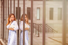 Businesswoman with cell phone. Close-up picture of businesswoman's reflection in the office building's glass wall. Smiling lady talking over mobile phone and Stock Photos