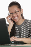 Businesswoman on cell phone and laptop Stock Images