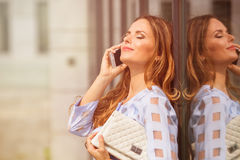 Businesswoman with cell phone. Portrait of businesswoman with her eyes closed. Pretty lady with long brown hair holding white little bag at her hand and talking Royalty Free Stock Photo