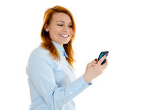 Businesswoman with cellphone. Young redheaded businesswoman smiling while reading message on her smartphone Royalty Free Stock Image
