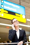 Businesswoman cellphone airport. Pretty young businesswoman talking on cell phone at airport Stock Photo