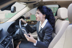 Businesswoman with cellphone driving car Royalty Free Stock Photo