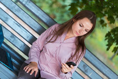 Businesswoman with cellphone and laptop in the park Stock Photography