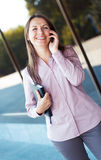 Businesswoman with cellphone and organizer while standing agains Royalty Free Stock Photos