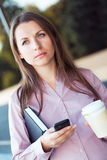 Businesswoman with cellphone and organizer while standing agains Royalty Free Stock Images