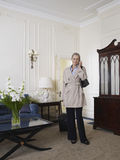 Businesswoman With Cellphone And Suitcase In Living Room Stock Photo