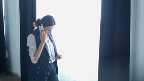 Businesswoman on cellphone talking, while using the other smartphone stock footage